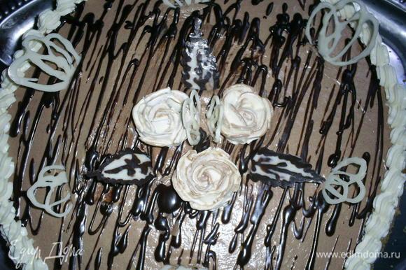 Приступаем к украшению торта. Я растопила шоколад. Нарисовала на файле завитушки и листочки. Подробные рекомендации как это сделать, можно посмотреть тут http://www.edimdoma.ru/posts/3649. Оставшимся черным шоколадом я нарисовала хаотичные полосочки на поверхности торта. Бока торта обсыпала оставшейся грильяжной крошкой. Из белого крема сделала розочки и бордюрчик. К тому времени шоколадный декор затвердел и я использовала его для украшения торта.