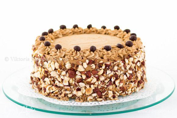 """Обмазываем торт сверху и по бокам, разравниваем. Из кондитерского мешка отсаживаем по краю торта """"розочки-цветочки"""". Бока обсыпать подсушенным и крупно порубленным фундуком. На каждую """"розочку"""" положить по кофейному зернышку в шоколаде. Дать настояться торту в холодильнике минимум 2 часа, лучше ночь."""