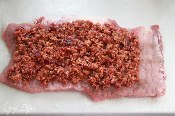 Подготовленный пласт свинины посолить, поперчить, выложить начинку, не выкладывая до края на 3 см.