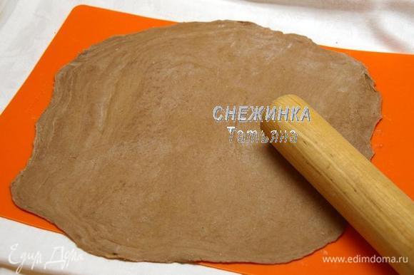Раскатываем одну часть теста в тонкий круг, присыпая рабочую поверхность мукой. Величина круга зависит от величины вашей сковороды или желаемого диаметра торта, если вы будете печь коржи на противне. Я пеку коржи на чугунной сковороде диаметром 22 см. Поэтому раскатываю круг диаметром чуть больше, около 23 см.