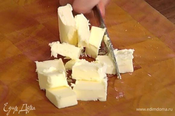 Предварительно охлажденное сливочное масло порубить небольшими кусочками.