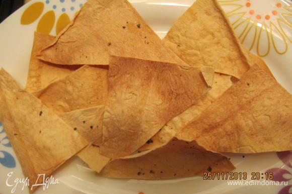 Включаем духовку. Чипсы. Кухонными ножницами нарезаем 1 лист лаваша на треугольники. Присыпаем солью, смесью перцем и базиликом. Отправляем в духовку на 5 минут.