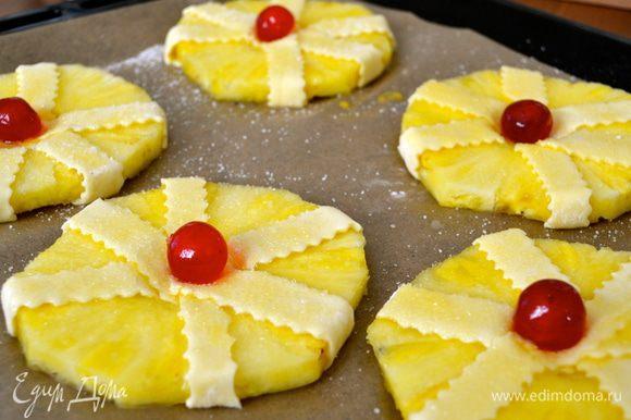 Выложить получившиеся пирожные на противень, смазать слегка взбитым яйцом и посыпать сахаром. В центр каждого положить по вишенке.