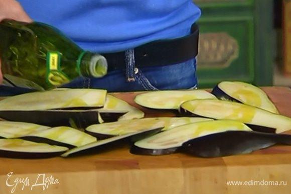 Баклажаны, удалив плодоножку, нарезать вдоль тонкими пластинами и сбрызнуть с каждой стороны оливковым маслом.