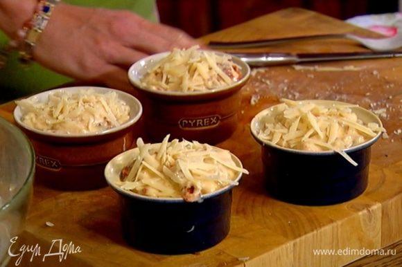 Небольшие керамические формочки для маффинов смазать оставшимся оливковым маслом, разложить в них тесто и посыпать сверху оставшимся сыром.