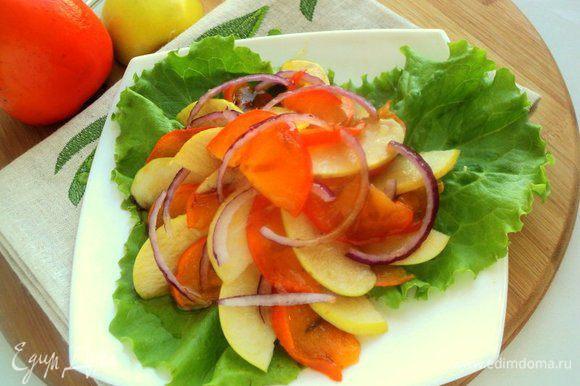 На блюдо выложить листья салата. Сверху разложить пластинки яблока и хурмы, чередуя их, и полукольца лука. Сверху полить соусом. Приятного аппетита!
