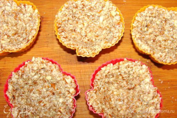 Разложить ореховую массу по формочкам так, чтобы остались углубления для начинки. Масса липкая, руки переодически можно смачивать. Убрать в морозилку не меньше чем на 30 минут.