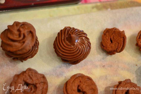 И отсадить из кондитерского мешка на каждую половинку небольшую порцию крема. Соединить второй половинкой. Можно печенье украсить растопленным шоколадом. Печенье охладить.