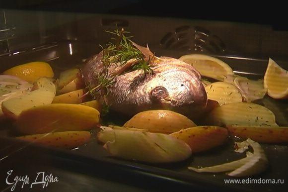 Понизить температуру в духовке до 200°С и запекать рыбу 15–18 минут.