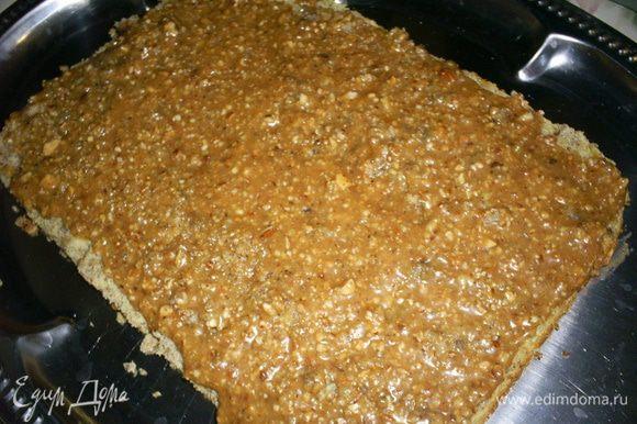 Приступаем к сборке торта. На блюдо кладем пласт бисквита срезом вверх, на него выкладываем половину карамельной прослойки, равномерно ее распределяем по поверхности.