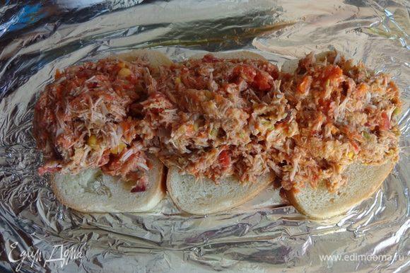На противень, застеленный фольгой и смазанный маслом уложить несколько кусочков хлеба, на них выложить фарш.