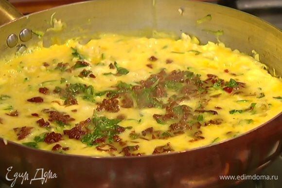 За несколько минут до готовности посыпать фриттату измельченными помидорами и базиликом.