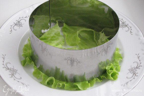 На тарелку выложить лист салата. Сверху поставить сервировочное кольцо.