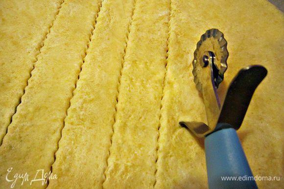 Противень застелить пекарской бумагой. Раскатать тесто и вырезать палочки с помощью ножа-ролика...