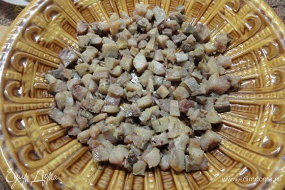 Сельдь очистить и разделать на филе без кожицы и косточек. Нарезать кубиками. Уложить на дно салатного блюда.