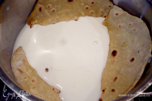 Каждую из лепешек раскатываем на щедро присыпанной мукой поверхности в тонкую лепешку диаметром примерно 20 см. Обжариваем лепешку на раскаленной сковороде, слегка смазанной оливковым маслом (мне помогала силиконовая кисточка) с каждой стороны до тех пор, пока на лепешке не начнут появляться коричневатые пузырьки. После обжаривания нескольких лепешек стоит вытирать сковороду сухим бумажным полотенцем, чтобы на ней не оставалось пригоревшей муки. Как только лепешка обжарилась сразу погружаем ее в молоко комнатной температуры.