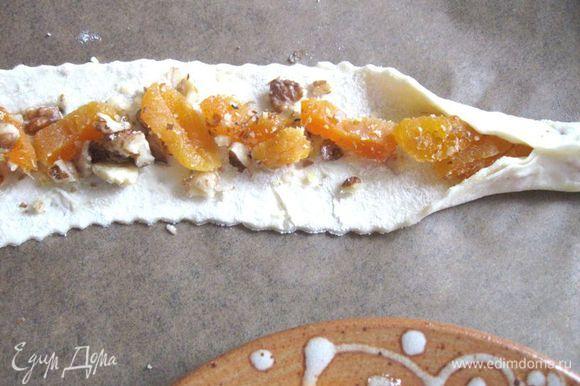 На противне, застеленном пекарской бумагой, разложить на каждой полоске теста поочередно начинки из айвы, чернослива, изюма, кураги. Защипнуть края теста.