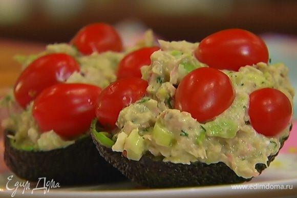 Чашечки авокадо наполнить начинкой, сверху выложить половинки помидоров.