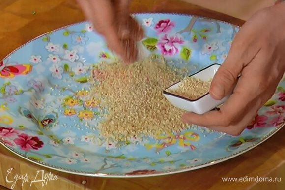 Небольшую часть сухарей высыпать на тарелку, добавить кунжутное семя и перемешать.