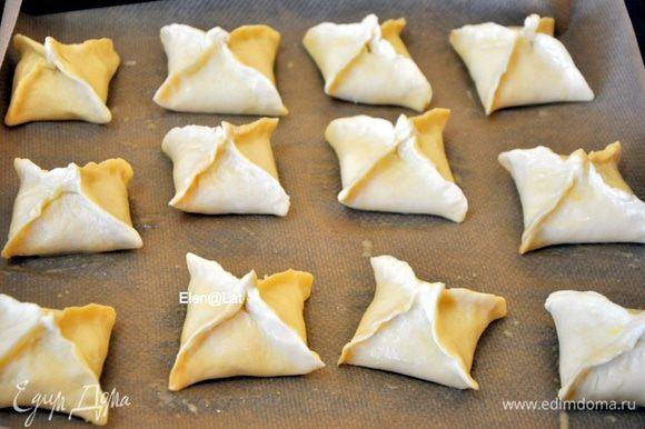Пирожки выложить на противень, застеленный пергаментом, смазать взбитым яйцом. И выпекать в заранее разогретой до 180 С духовке примерно 25-30 минут.