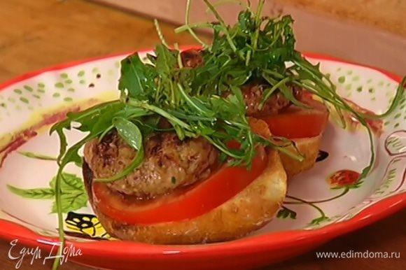 На обжаренный хлеб выложить кружки помидора и котлетки, а сверху листья руколы.