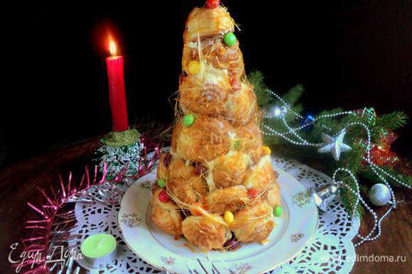 Осторожно снять бумажный конус и установить торт из профитролей на блюдо. Две вилки соединить спинками, окунуть в горячую карамель и разъединяя и соединяя вилки, вытянуть карамельные нити, обматывая ими крокенбуш. Дополнительно можно прикрепить на торт с помощью карамели разноцветные конфетки ММ. С Новым Годом и приятного аппетита!