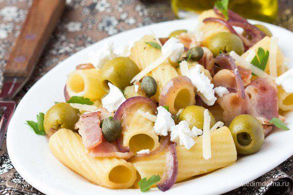 Выкладываем по тарелкам пасту с соусом. Сверху присыпаем натертым твердым сыром, фетой и рубленной зеленью петрушки.