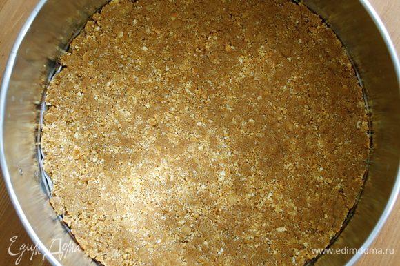 В разъемную форму (24 см) выложить мокрую крошку печенья и разровнять по дну формы. Убрать в холодильник на полчаса.
