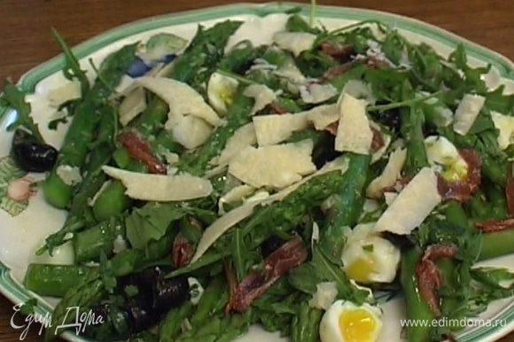 Полить салат заправкой, добавить анчоусы, посыпать руколой и натертым сыром.
