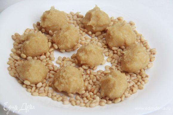 Тесто вынуть из холодильника, разделить на 10 частей, каждую скатать в шар. Миндальные шарики выложить на орешки, слегка придавить.