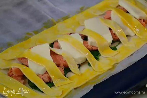 Полоски выложить сверху на начинку и прижать руками к краям, смазанным яйцом.