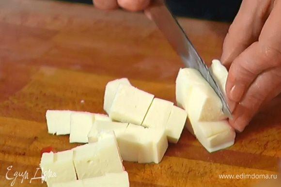Моцареллу нарезать кубиками и выложить в сковороду к помидорам.