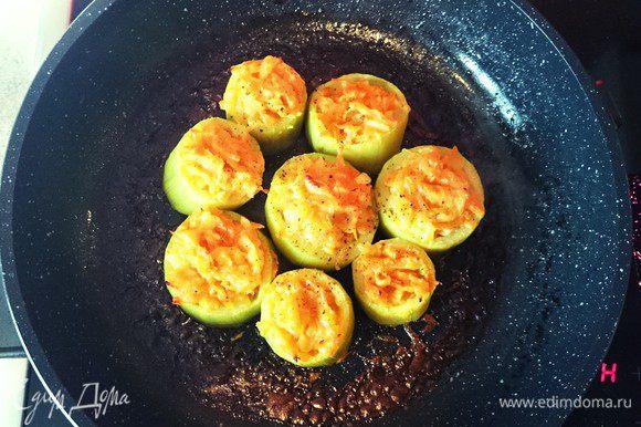 Кабачки откинуть на сито и наполнить овощным фаршем. Поставить в разогретую до 180 г духовку. Запекать 20-30 минут. При подаче оформить зеленью.