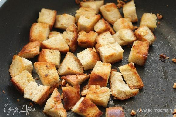 В сковородке разогреть 1-2 ст. л. оливкового масла, выдавить туда же дольку чеснока, порезать хлеб кубиками и обжарить.