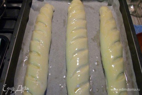 Оставляем на час, потом смазываем яичным желтком, делаем наше зеленое масло, мягкое масло смешиваем с зеленью, я беру зеленый чеснок или укроп с чесноком и измельчаем в блендере, готовый багет разрезаем в тех самых надрезах и ножом засовываем масло во все надрезы.