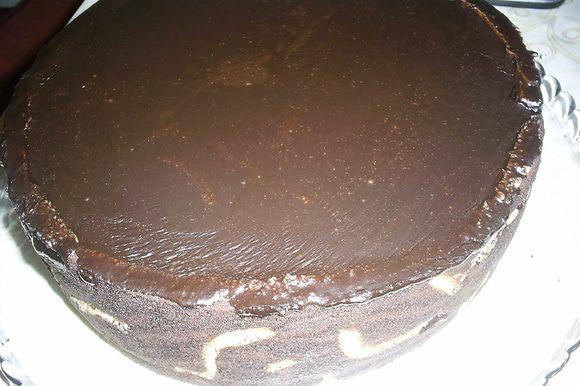 Заливаем торт глазурью комнатной температуры и отправляем в холодильник на ночь. Если будут лишние бортики из теста, их надо обрезать острым ножом.