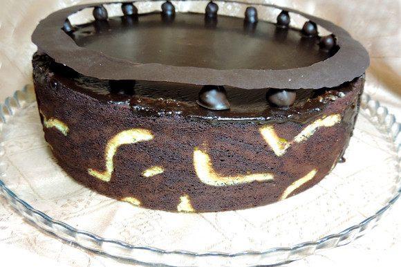 Для украшения нарисуйте на пергаменте растопленным шоколадом обод, больший диаметр которого равен диаметру формы (25 см). Дайте застыть и затвердеть при комнатной температуре. В холодильнике он деформируется! По краю торта в оригинале надо выставить 12 крупных ягодок свежей малины. У меня ее не было и я заменила малину фундуком в шоколаде. Для этого окунула очищенный обжаренный фундук в растопленный шоколад и дала застыть. Сверху на фундук (малину) перед подачей аккуратно устанавливаем шоколадный обод.