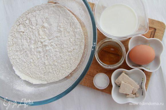 Муку просеять. Подготовить остальные ингредиенты для теста: молоко слегка подогреть и развести в нём дрожжи, мёд и соль; туда же вбить яйцо. Соединить муку с молочной смесью.