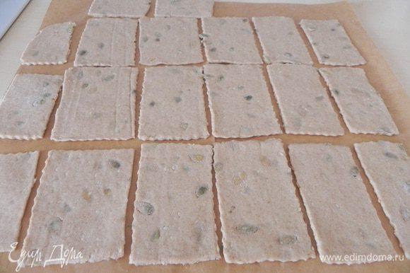 Тонко раскатайте тесто на листе пергамента. Разрежьте на прямоугольники.