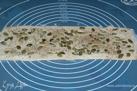 Берем пласт теста, не раскатываем, посыпаем солью, перцем и тыквенными семечками. Слегка прокатываем скалкой, чтобы посыпка приклеилась к поверхности теста. Смазываем растительным маслом.