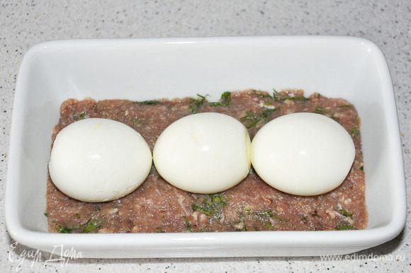 Яйца сварить (минут 7). Выложить треть фарша в форму, выложить яйца.