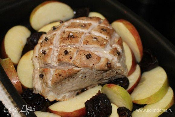 Чернослив замочить в теплой воде на 15 минут. Яблоки вымыть, удалить сердцевину и нарезать дольками. Вынимаем форму из духовки, выкладывает яблоки и чернослив вокруг мяса. Кусок мяса поливаем сверху медом и присыпаем сахарной пудрой, отправляем в духовку на 20 минут,через 10 минут переворачиваем дольки яблок.