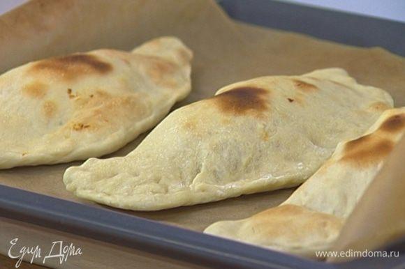 Уложить пиццы на противень, застеленный бумагой для выпечки, смазать оливковым маслом и выпекать в разогретой духовке 15‒20 минут.