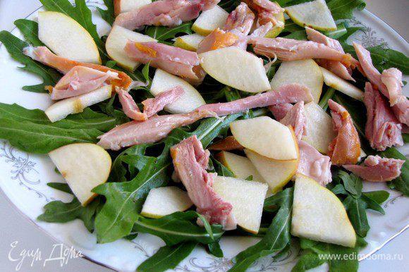 На салатную зелень сверху выложить кусочки мяса и груши.