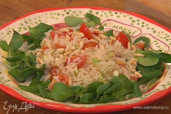 Листья салата разложить на тарелке, сверху выложить заправленный рис и присыпать кедровыми орехами.