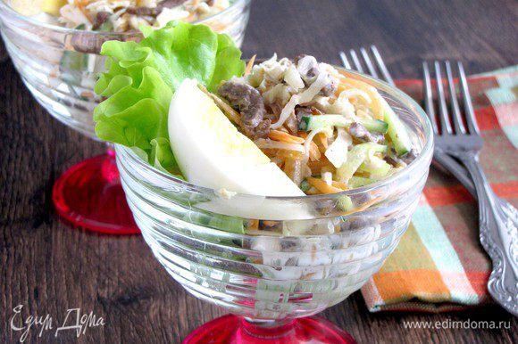 В креманки положить по одному салатному листу, выложить салат. Добавить майонез и украсить четвертинкой отварного яйца.