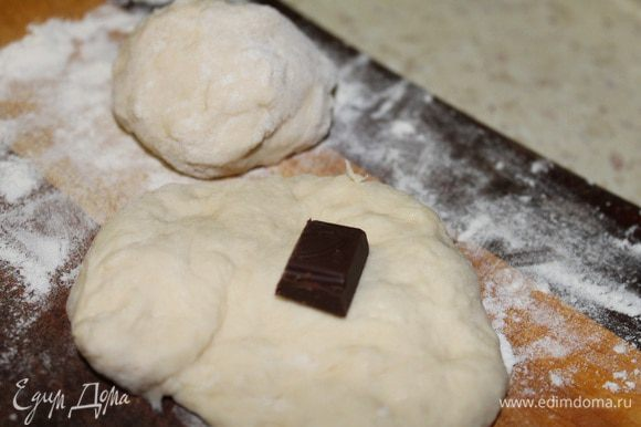 Отщипываем кусочек теста, расплющиваем его в ладошке, кладем кубик шоколада, хорошо защипываем края собирая их к центру, чтобы получился колобок. Масло выливаем в ковш и обжариваем пончики на среднем огне с двух сторон, до золотистого цвета.