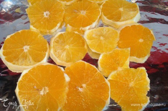 Очистите апельсины, нарежьте кружочками, выложите на противень застеленный фольгой.