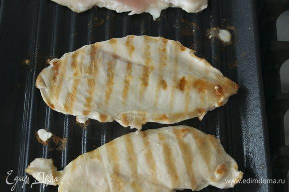 В это время приготовьте начинку-салат. Разогрейте сковороду-гриль и смажьте решетку слегка маслом. Куриные грудки обжарьте по 8 минут с каждой стороны или пока сок при прокалывании не станет прозрачным.
