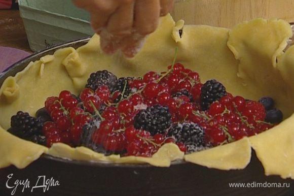 Выложить на тесто ягоды, немного присыпать их сахаром и загнуть края теста, накрыв им ягоды — середина должна остаться открытой.